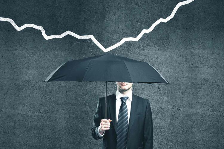homme d'affaire  se protégeant d'une chute de chiffres d'affaire avec une parapluie