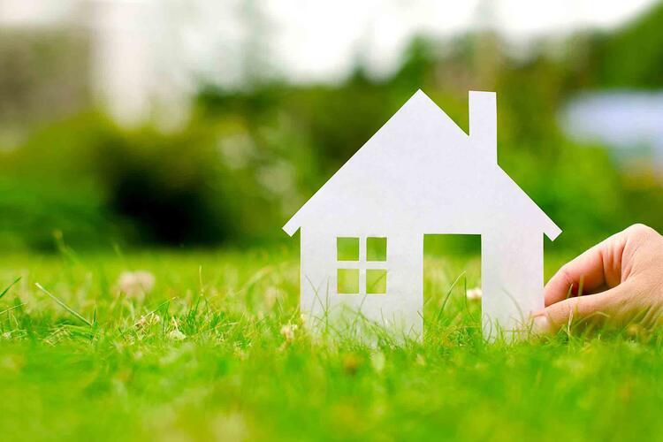 petite maison blanche tenue par une main sur de l'herbe